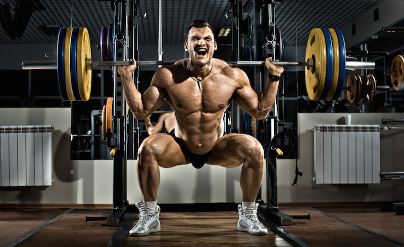very brawny guy bodybuilder , execute exercise squatting with weight, in gym